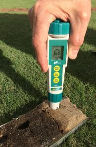Direct Soil pH Pen being used with the Mascaro Profile Sampler showing a reading of 6.80 in the roots zone about three inches deep