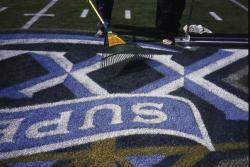 This is the field logo for SuperBowl XXXIX at Alltel Stadium, Jacksonville, Florida being hand raked to stand the grass up for a second painting.