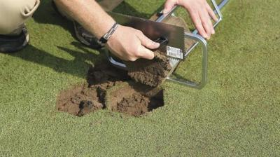 Scraping bottom of plug flat on 7 Inch Hexagon Turf Plugger with trowel provided with unit